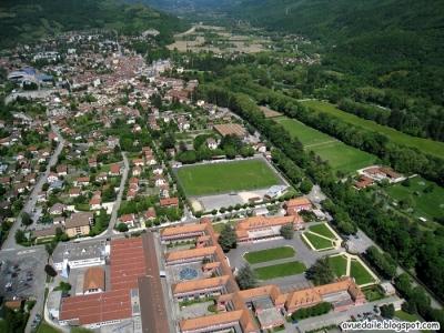 vue plongeante sur la ville de Vizille : au 1 er plan le lycée professionnel de Vizille (ouvert en 1933) et son parc (hébergement des participants) , puis le stade de rugby( parking des campings cars ), et en face le parc du château ou se tiendra l' accueil du BRA 2013 (+ quelques places de camping - sans accès voitures )